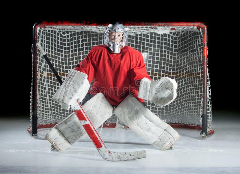 Un portero joven del hielo-hockey en una posición lista contra una oscuridad imágenes de archivo libres de regalías