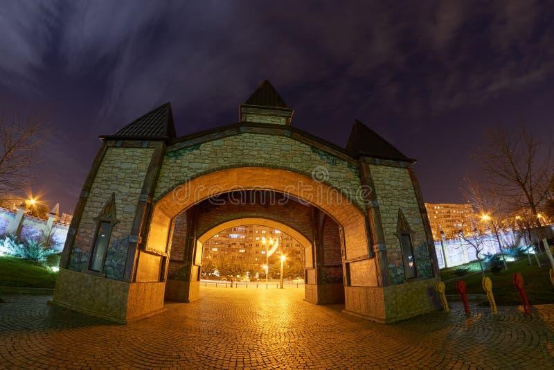 Un portone di un parco di distrazione alla notte variopinta con le luci alla notte immagini stock