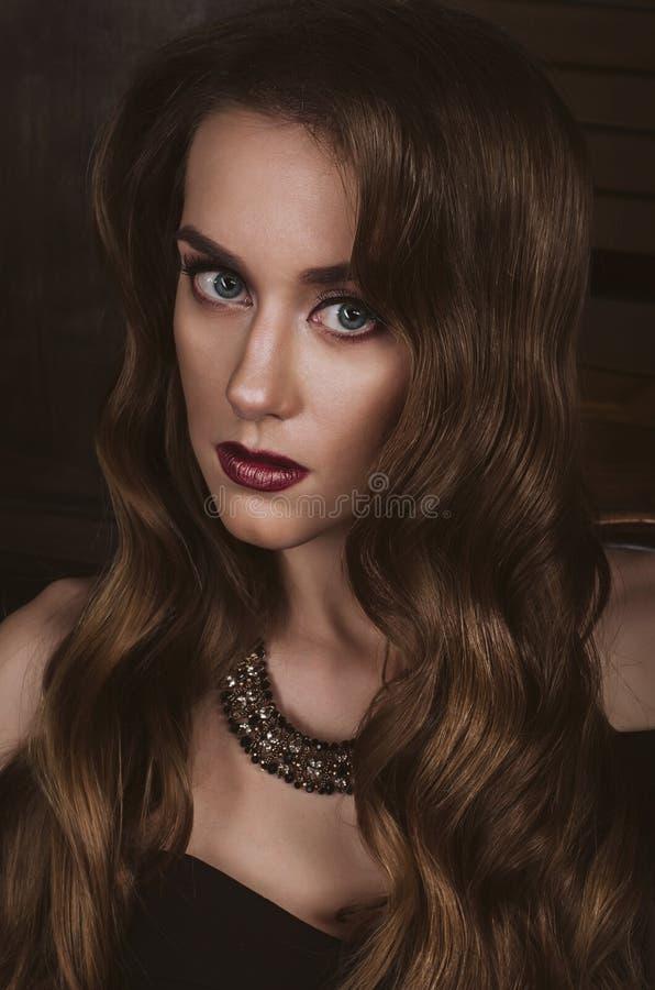 Un portrait étroit d'une femme châtain attirante avec une coupe de cheveux dans le style d'une vague de Hollywood, dans une robe  photographie stock