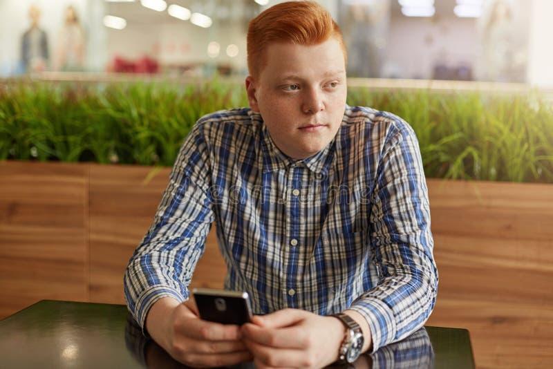 Un portrait d'adolescent réfléchi avec les cheveux rouges et les taches de rousseur utilisant la chemise vérifiée tenant le télép image stock