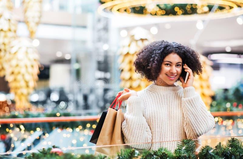 Un portrait d'adolescente avec le smartphone et les sacs en papier au centre commercial à Noël photos libres de droits