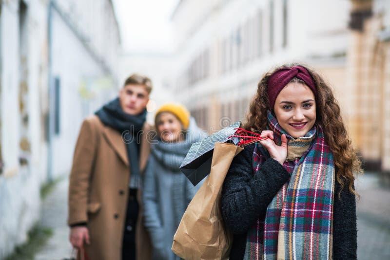 Un portrait d'adolescente avec les paniers de papier sur la rue en hiver image stock