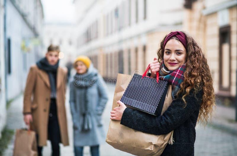 Un portrait d'adolescente avec les paniers de papier sur la rue en hiver photo stock