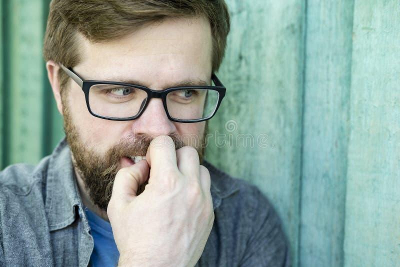 Un portrait d'un adroit, déloyal, traçant quelque chose homme mesquin qui regarde au côté, découvre ses dents et tient le sien photos stock