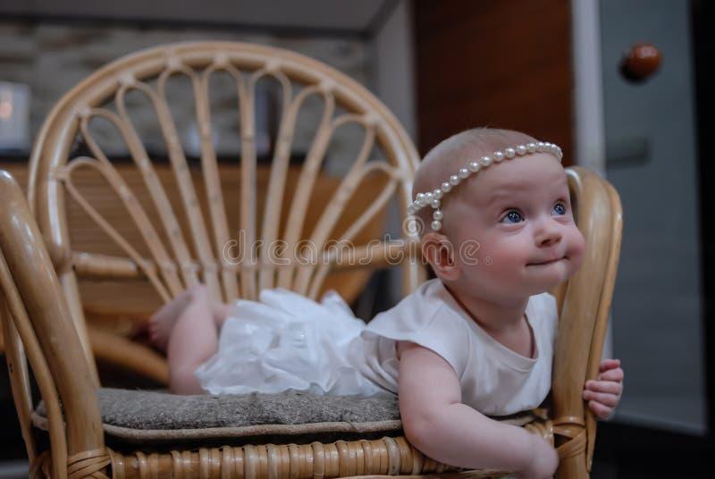 Un portrait d'un bébé de cinq mois avec les yeux bleus clairs dans une robe blanche et un bandeau nacré image libre de droits