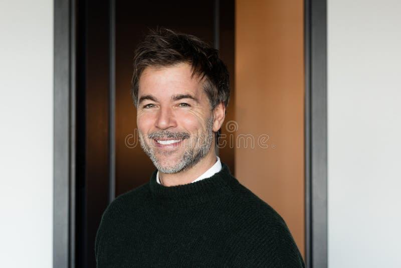 Un portrait d'un homme barbu d'une cinquantaine d'années souriant sur un fond en bois photos libres de droits