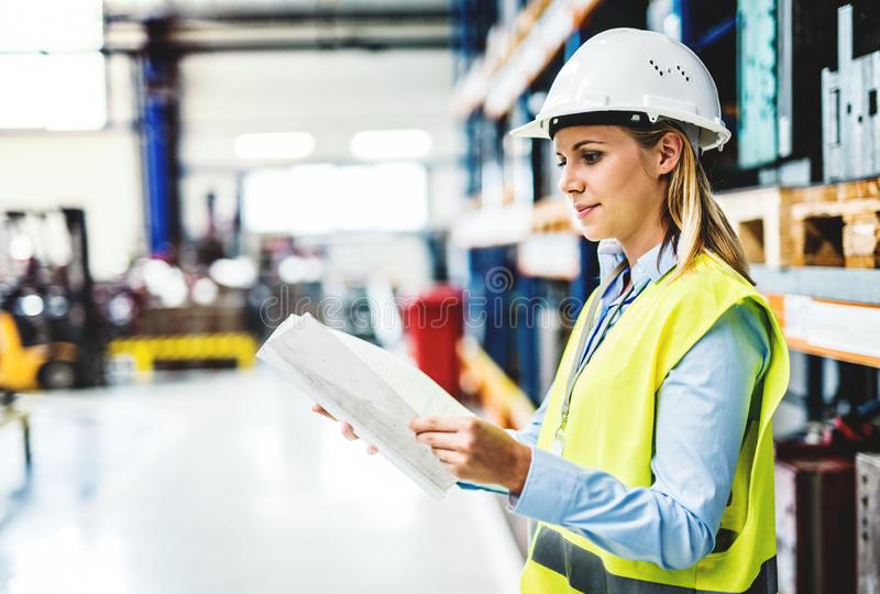 Un portrait d'un ingénieur industriel de femme dans une usine tenant des écritures image stock