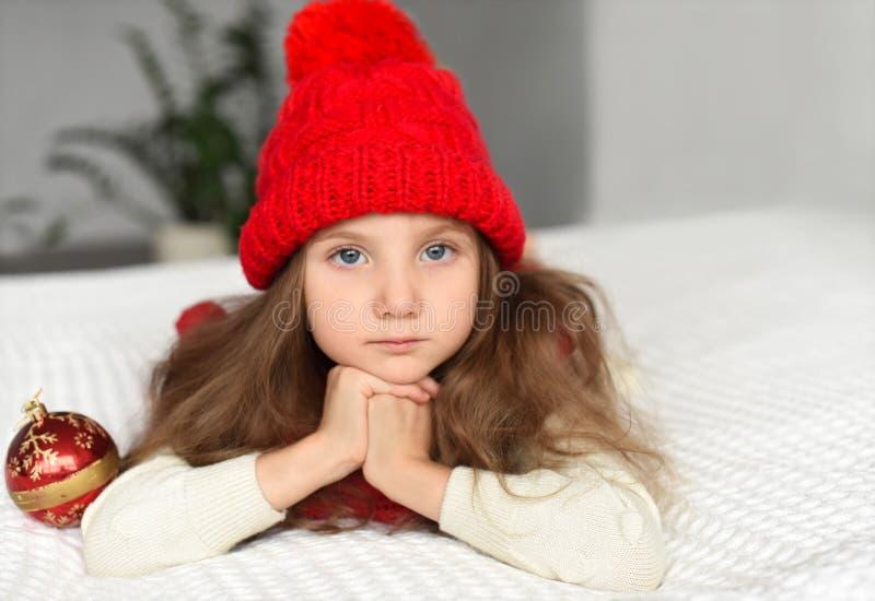 Un portrait d'intérieur d'une petite fille dans un chapeau rouge chaud tricoté tenant des décorations de Noël - une photo représe image stock