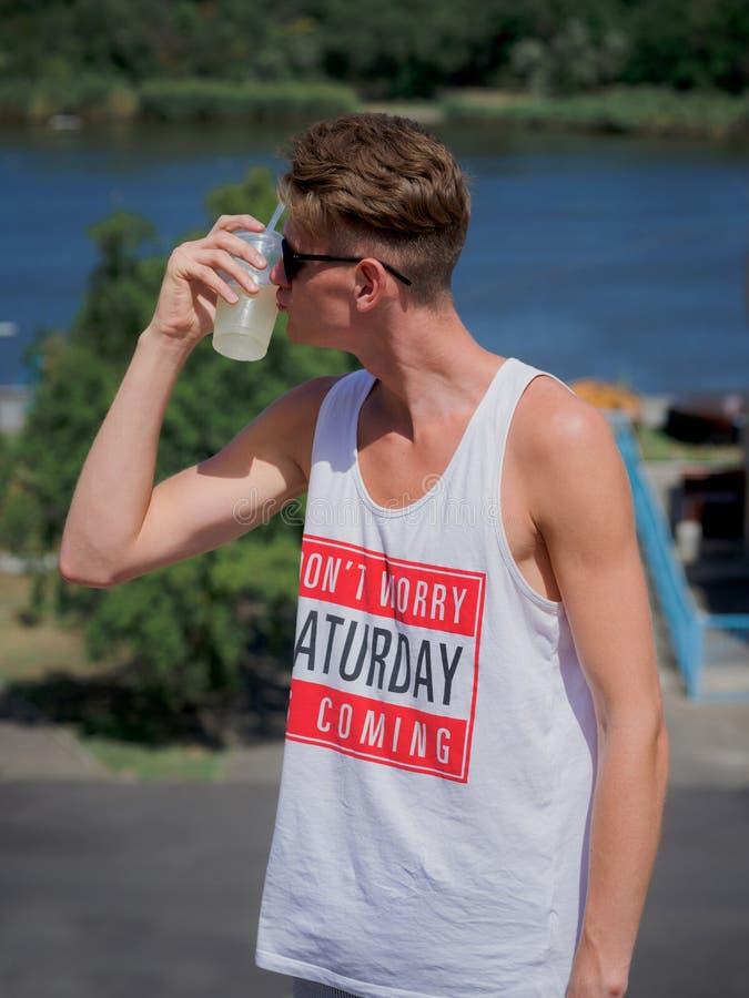 Un portrait d'un jeune homme embrassant une limonade sur un fond brouillé de rivière Un type élégant dans des lunettes de soleil  images stock