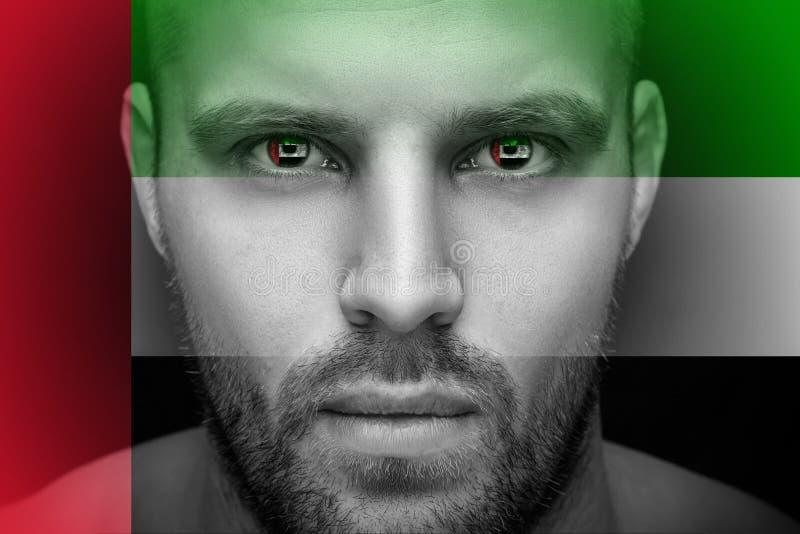 Un portrait d'un jeune homme sérieux, dans lequel les yeux est reflété le drapeau national photo stock