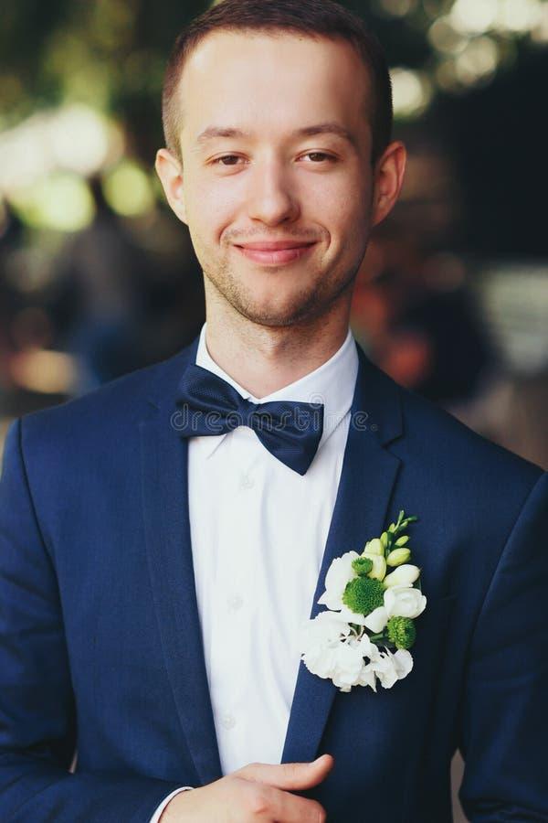 Un portrait d'un marié dans le costume bleu avec le boutonni vert et blanc photographie stock libre de droits