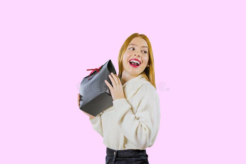 Un portrait d'une belle fille rousse mignonne qui tient un sac de cadeau dans une boîte noire avec un ruban rouge de velours soul photo stock