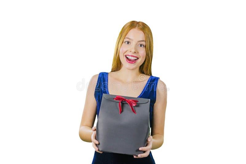 Un portrait d'une belle jeune fille rousse dans une robe égalisante sur qui tient un présent dans des ses bras tout en essayant photos stock