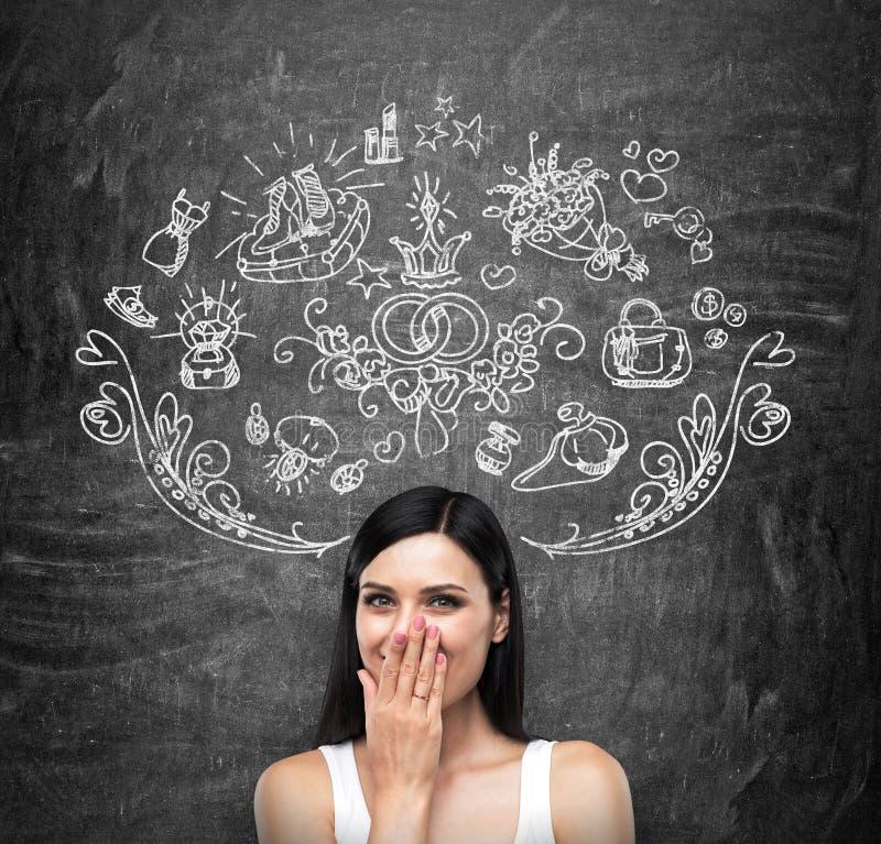 Un portrait d'une dame heureuse de brune dans un dessus de réservoir blanc qui couvre sa bouche par la main et rêve des achats Sh image libre de droits