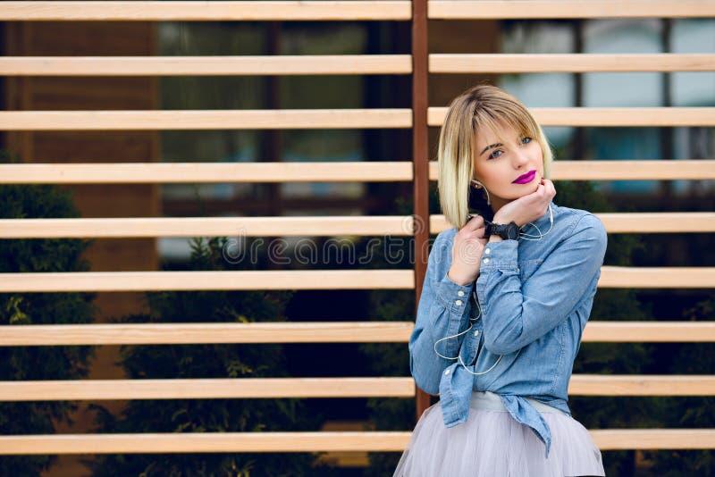 Un portrait d'une fille blonde rêveuse avec les lèvres roses lumineuses et le maquillage nu écoutant la musique sur un smartphone photographie stock libre de droits