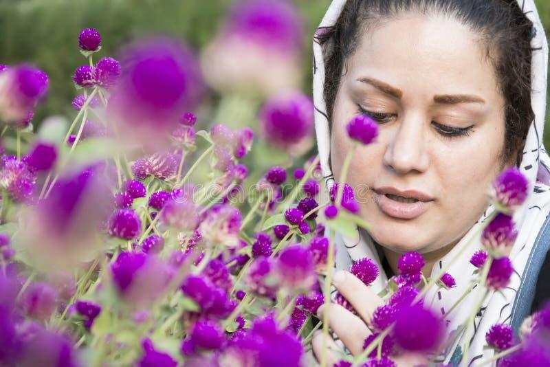 Un portrait d'une jeune belle femme musulmane dans un châle blanc devant les fleurs pourpres images stock
