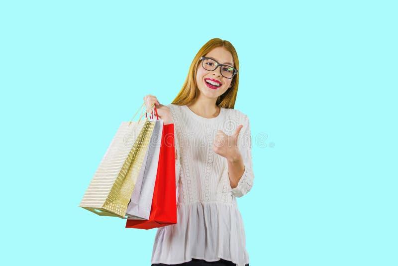 Un portrait d'une jeune fille rousse dans un chemisier blanc avec les sacs colorés de vacances qui tient ses mains avec une photos libres de droits