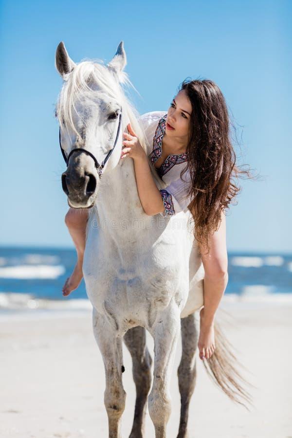 Un portrait d'une jeune fille s'asseyant sur un cheval blanc image libre de droits