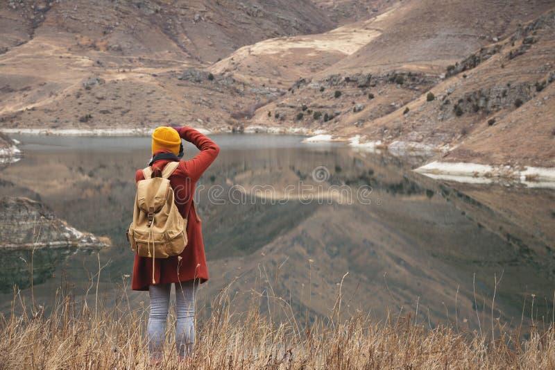 Un portrait de derrière d'une voyageuse de fille prendre une photo sur le fond d'un lac dans les montagnes en automne ou image stock