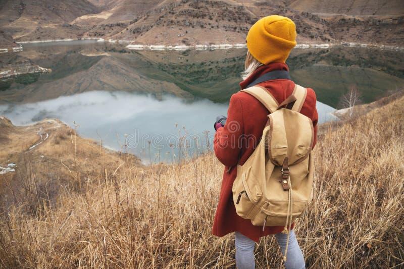 Un portrait de derrière d'un voyageur de photographe de fille sur le fond d'un lac dans les montagnes en automne ou tôt photos stock