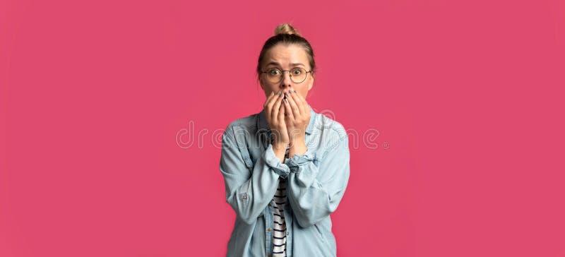 Un portrait de femme blonde, elle étonnant choque et garde ses mains près de la bouche photo libre de droits