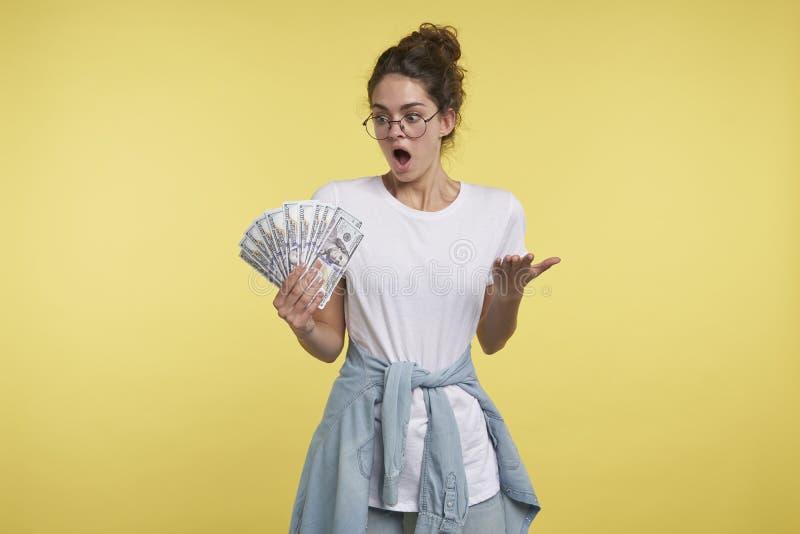 Un portrait de femme choquée de brune, elle peut le ` t la croire a tellement l'argent dans la main photographie stock libre de droits