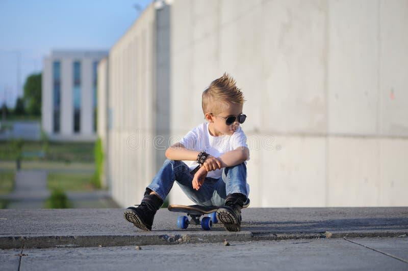 Un portrait de garçon provoquant avec la planche à roulettes dehors photo stock