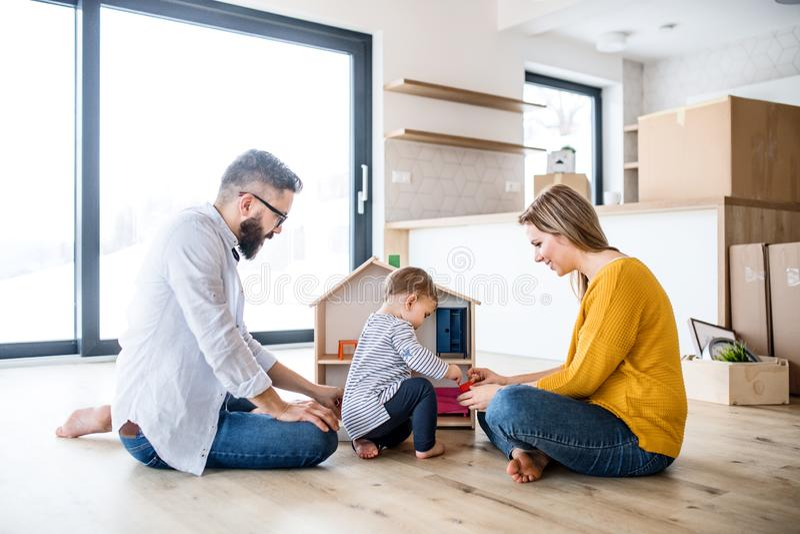 Un portrait de jeune famille avec une fille d'enfant en bas âge se déplaçant la nouvelle maison, jouant photos libres de droits