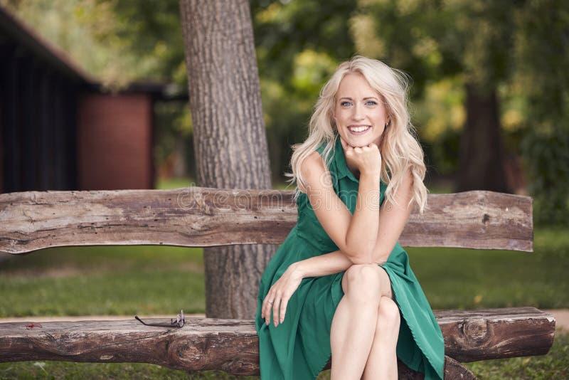 Un portrait de jeune femme, se reposant dans le banc en bois, robe de vert, 25 années, sourire heureux, regardant à l'appareil-ph photo stock