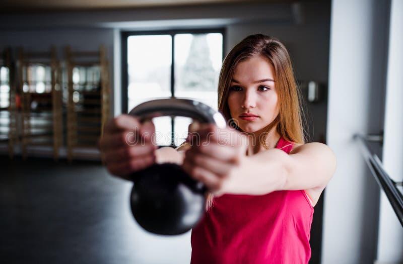 Un portrait de la jeune fille ou de la femme faisant l'exercice avec un kettlebell dans un gymnase photo stock