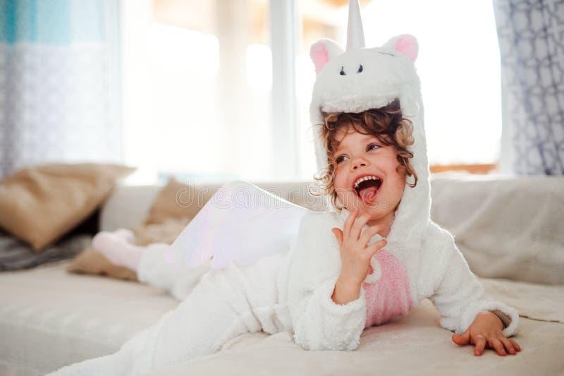 Un portrait de petite fille dans le masque de licorne se trouvant sur le sofa à la maison photographie stock