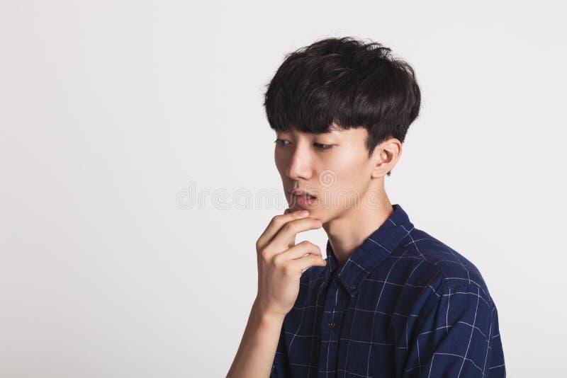Un portrait de studio d'un jeune homme asiatique qui est préoccupé et profond dans la pensée photos libres de droits