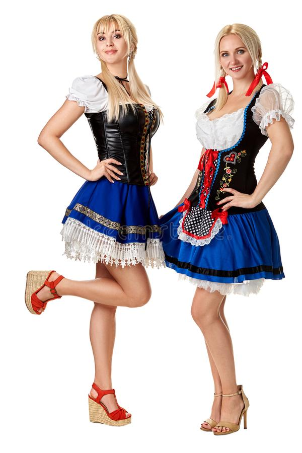 Un portrait intégral de deux belles femmes dans un costume traditionnel d'isolement sur le blanc oktoberfest photo libre de droits
