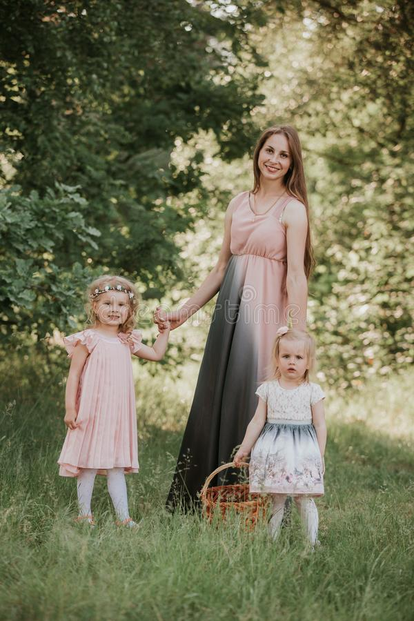 Un portrait merveilleux de maman avec deux filles en parc M?re et tourbillonnement de deux filles photographie stock libre de droits