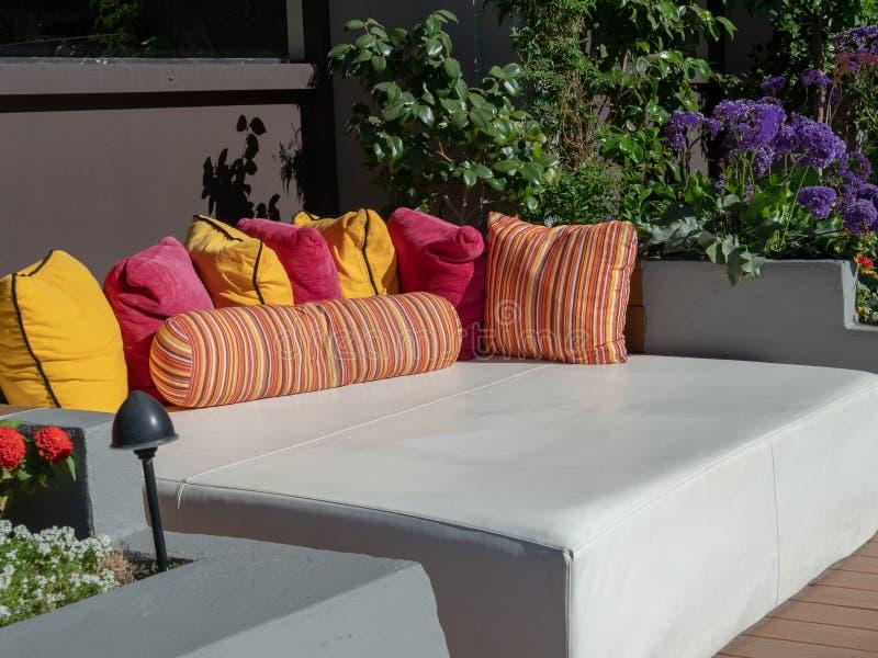 Un posto letto per ricoveri giornalieri all'aperto e cuscini della stazione balneare pronti per bighellonare al poolside immagine stock