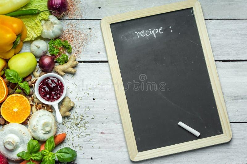 Un posto per scrivere il vostro proprio menu o ricetta - lavagna, gesso e lotti della frutta, delle verdure e delle erbe immagine stock