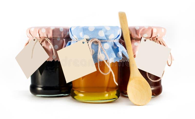 Un pot avec du miel, la mûre et la fleur bloquent sur un fond blanc images stock