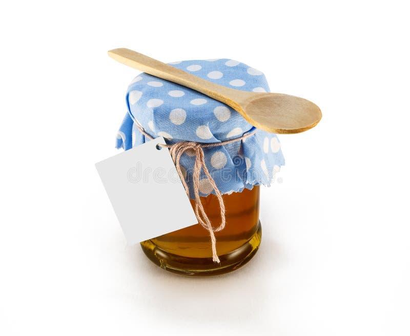 Un pot avec du miel, la mûre et la fleur bloquent sur un fond blanc photographie stock