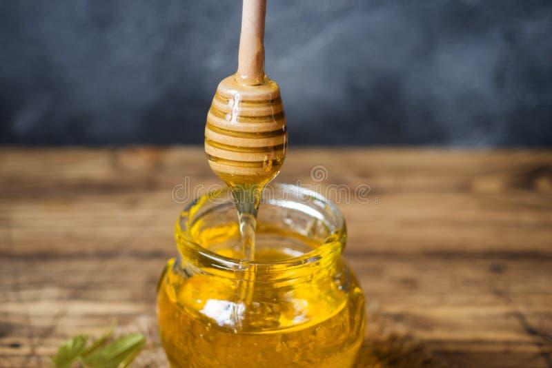 Un pot de miel liquide des fleurs de tilleul et d'un bâton avec du miel sur un fond foncé Copiez l'espace photo libre de droits