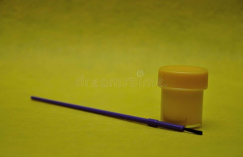 Un pot de peinture jaune avec un pinceau pourpre image libre de droits