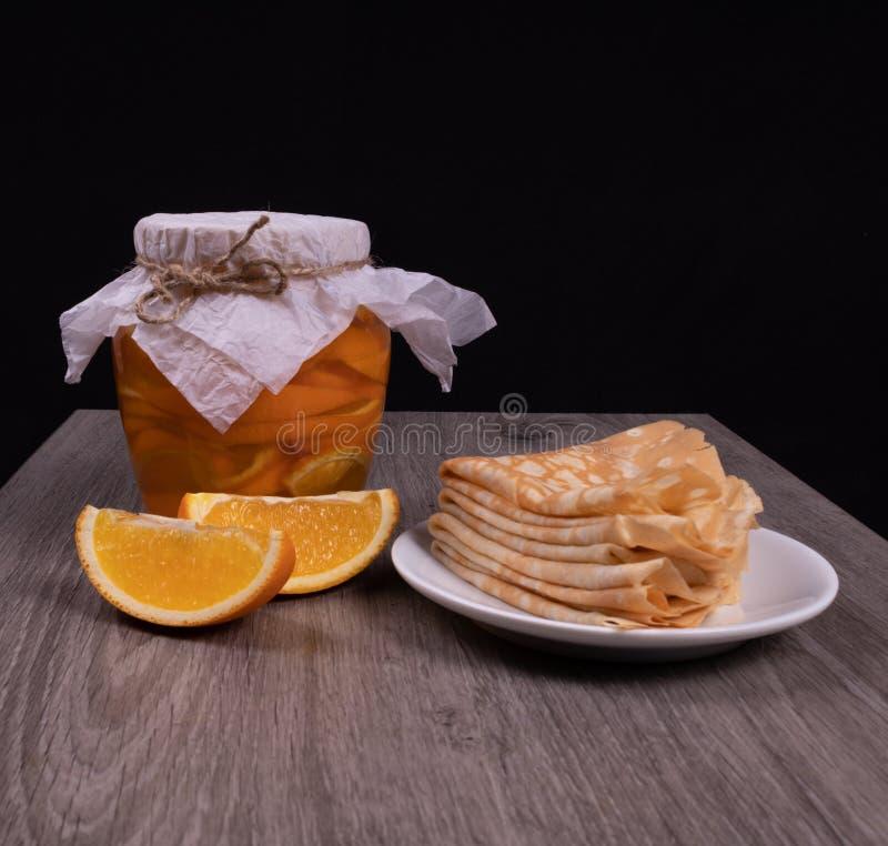 Un pot de sirop orange avec les tranches oranges ? c?t? d'un plat des cr?pes frites sur une surface en bois avec un fond noir image libre de droits