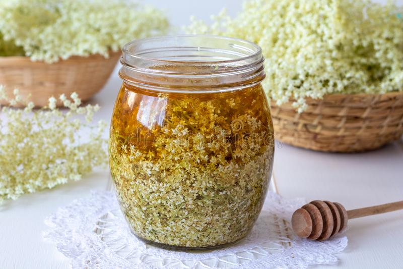 Un pot a rempli de fleurs et de miel frais d'aîné, pour préparer le syru image stock