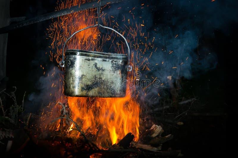 Un pote de agua hirvienda en el fuego en el bosque foto de archivo libre de regalías