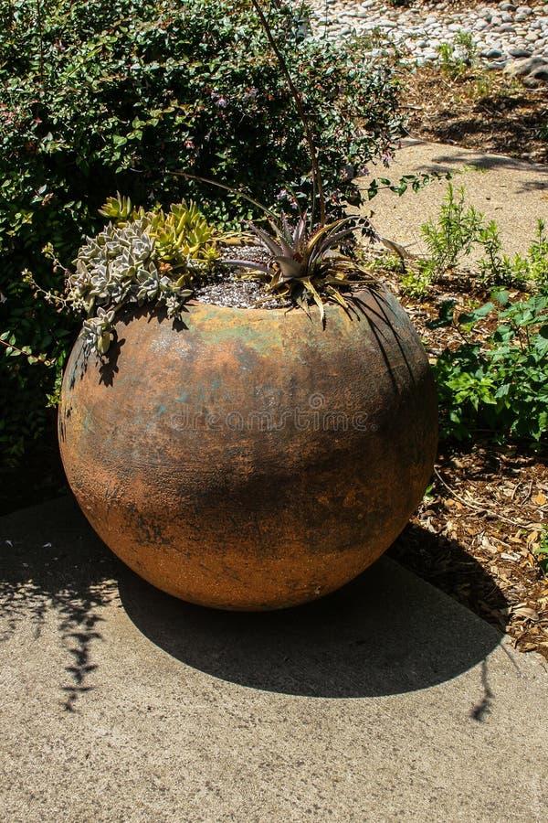 Un pote de arcilla grande en un jardín imagenes de archivo