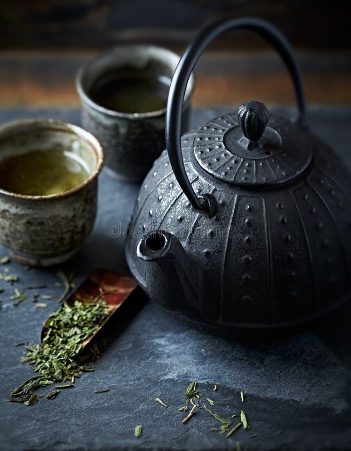 Un pote del té del arrabio y un té verde en tazas de cerámica imagenes de archivo