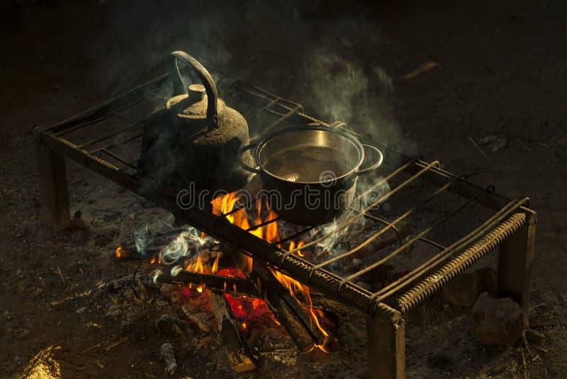 Un pote y una caldera en un hogar portátil hecho de las barras de metal en una vivienda del ` s del nómada fotografía de archivo