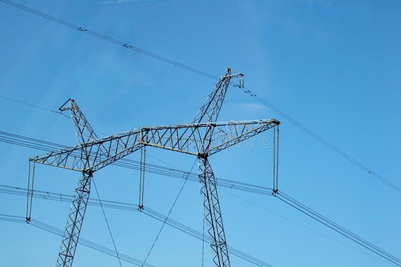 Un poteau des réseaux et des fils électriques contre le ciel bleu photographie stock