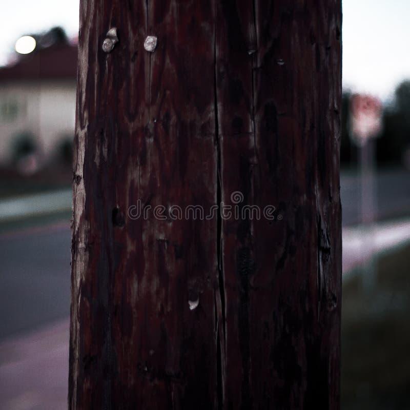 Un poteau en bois sur un fond suburbain de tache floue photos stock