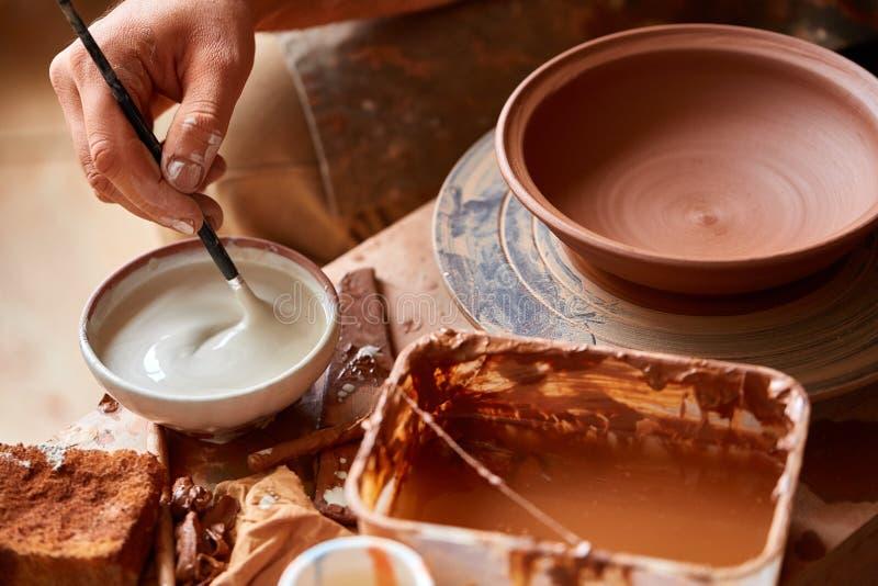 Un potier disposent des peintures pour teindre un plat d'argile dans un blanc dans l'atelier, vue supérieure, plan rapproché, foy image libre de droits
