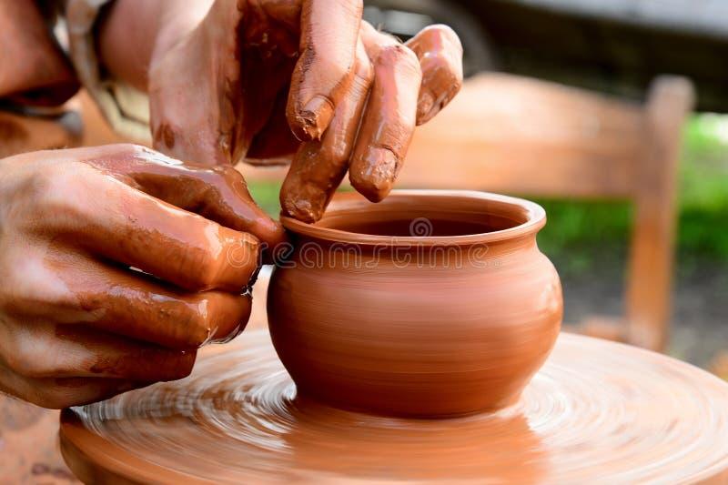 Un potier forme un pot d'argile photographie stock